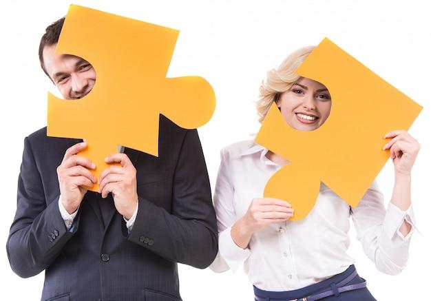 ビジネスマンおよび女性のパズルのジグソーパズルのピースに参加します。