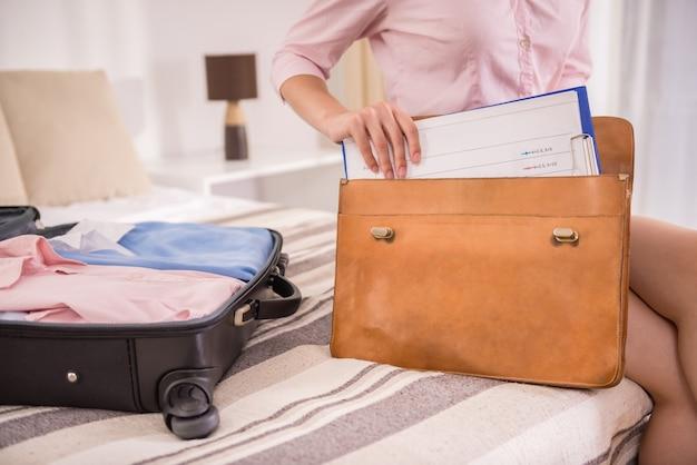 ビジネスの女性はブリーフケースに彼のものを梱包します。