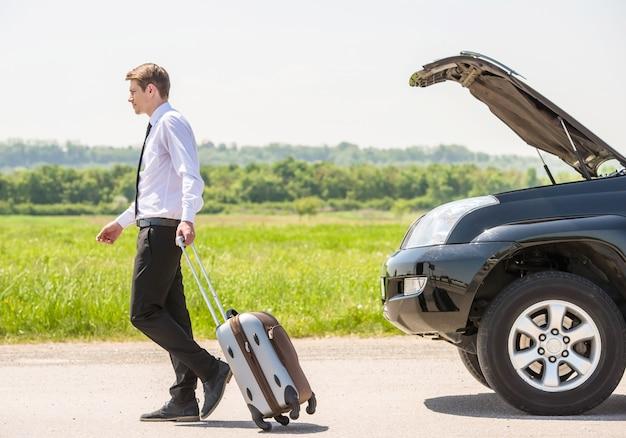 スーツケースを持った若いビジネスマンの完全な長さの側面図。