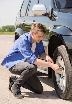 若い男が彼の車にパンクしたタイヤを変更します。