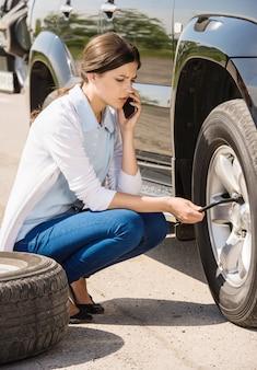 若い女性が彼の車にパンクしたタイヤを変更します。