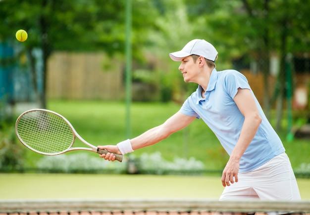 若い魅力的な男は、朝のコートでテニスをします。