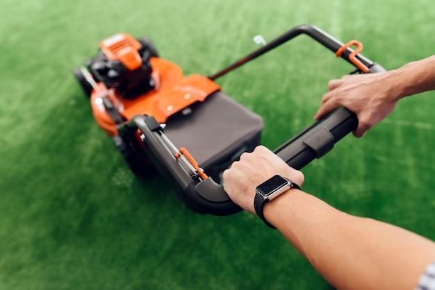 男はハンドルの芝刈り機を持っています。