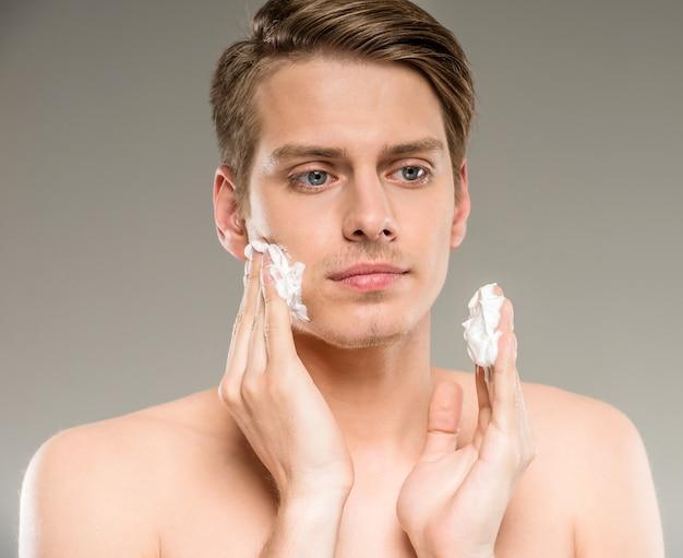 若い男は彼の顔にシェービングクリームを適用しています。