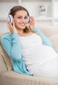 ソファに座って音楽を楽しんでいる女性。