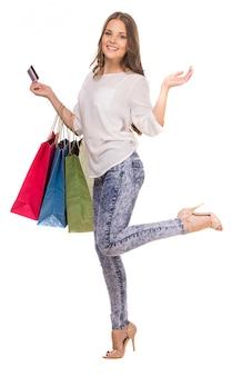 色の買い物袋を保持している陽気な女性。