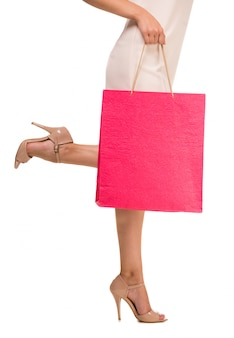 ピンクの買い物袋を保持している女性