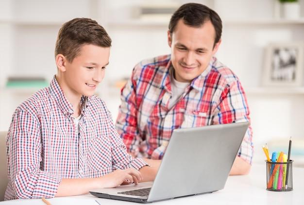 Отец и сын, используя ноутбук вместе дома.