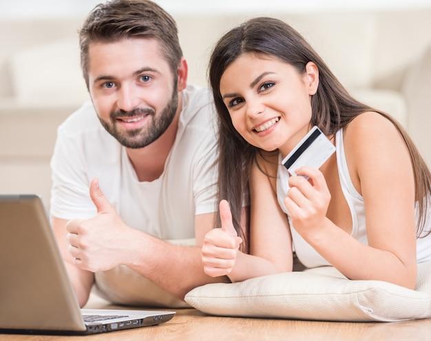 自宅の床に横たわって、オンラインで注文するカップル。