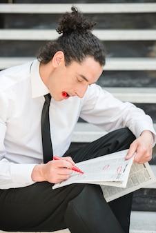 男は新聞で階段に座って仕事を探しています。