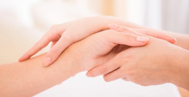 ヘルススパでハンドマッサージを受ける女性。
