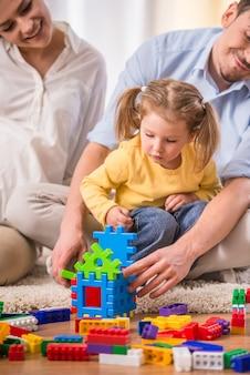 妊娠中の母親と若い父親は娘と遊んでいます。