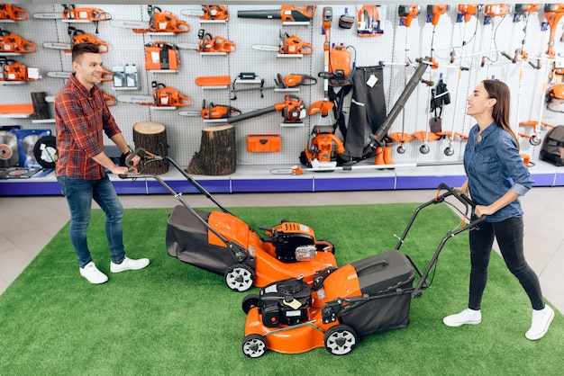 人々は店で芝刈り機をテストしています。