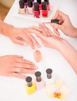 女性は柔らかい白いタオルにマニキュアで爪します。