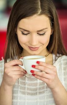 女の子は一杯のコーヒーで都会のカフェに座っています。