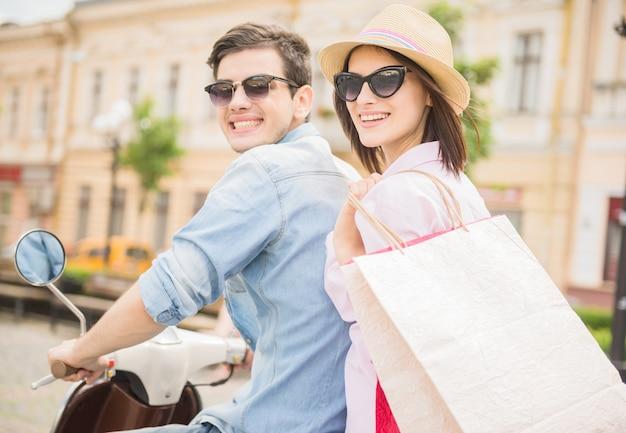 若いカップルが一緒にスクーターに乗っての背面図。