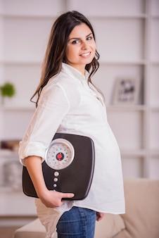 妊娠中の成人女性が自宅で体重計を保持しています。