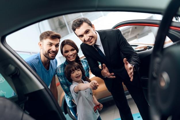 若い家族がサロンで新しい車を選んでいます。