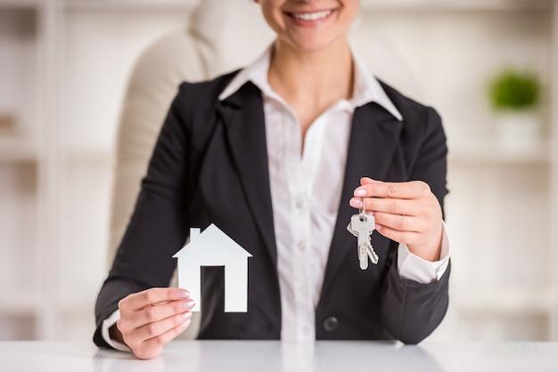 女性は販売サインとキーの家を見せています。