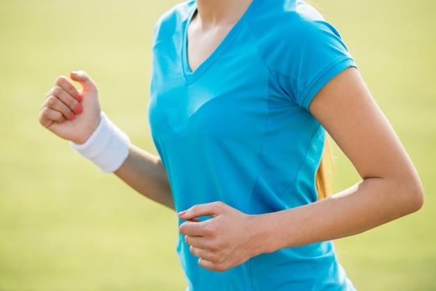 日の出屋外で走っている女性のクローズアップ。
