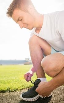 Крупным планом спортивный человек, сидящий на дороге и завязывать шнурки.