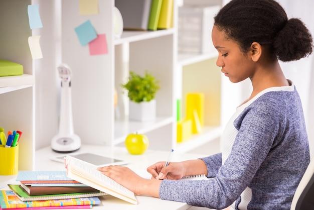 若い可愛いムラート女子高生はテーブルに座っています。