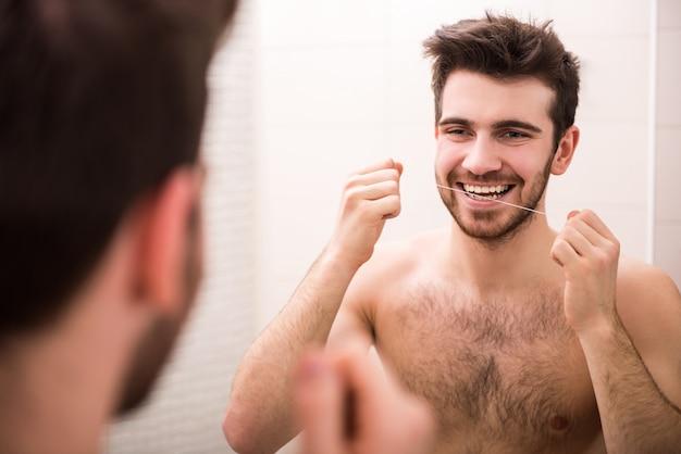 男は鏡を見て歯をフロスします。