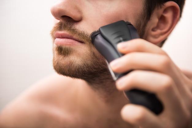 浴室で剃るためのかみそりで剃る男。