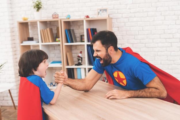スーパーヒーローのスーツを着た父と子。