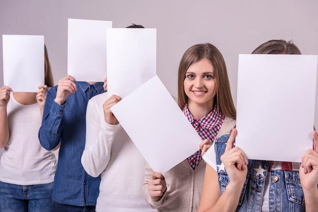 ホワイトボードを保持している若いグループと彼らの顔をカバーします。
