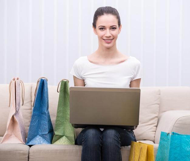 Женщина использует ноутбук, сидя на диване.
