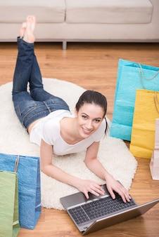 Счастливая усмехаясь женщина с хозяйственными сумками использует компьтер-книжку.