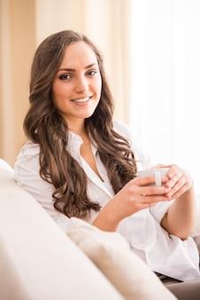 ソファの上のコーヒーと笑顔の女性
