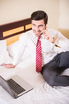 男はコンピューターの近くに座って電話で話します。