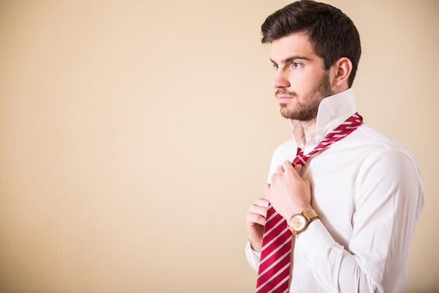 男は首のネクタイをまっすぐにします。