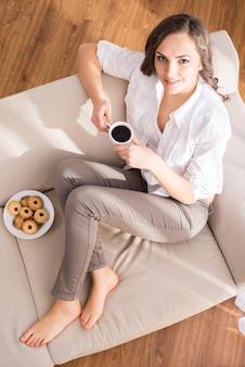 一杯のコーヒーを持つ若い女性の平面図です。
