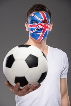 英国を示すために彼の顔に描かれた旗を持つ若い男。