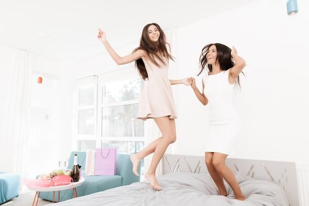 ベールの中の女の子がベッドの上でジャンプしています。
