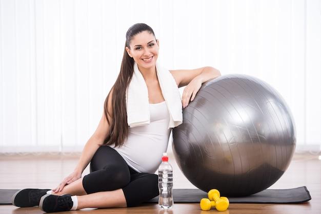 Беременная женщина делает упражнения с гимнастическим мячом.