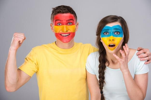 Два фаната с флагами своих стран, нарисованными на лицах.