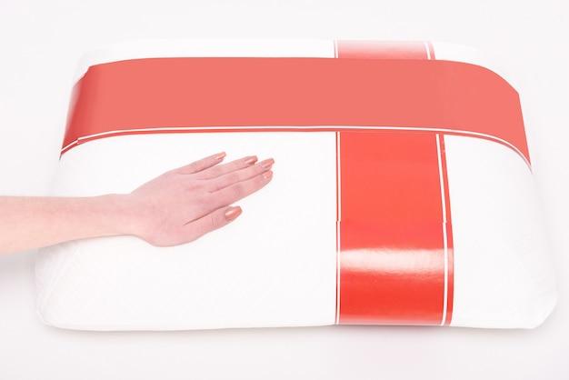 柔らかい枕を持つ若い女性の手。