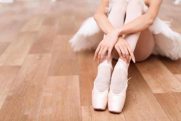 プロのバレリーナが床に座っています。