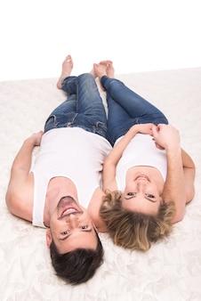 Вид сверху молодой пары лежат на качественном матрасе.
