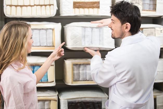 セールスマンは、店内の高品質マットレスについて顧客に伝えます。