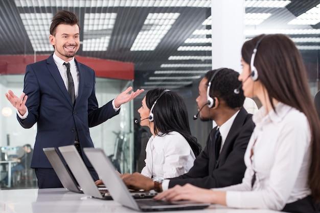 マネージャーは、コールセンターの従業員に何かを説明しています。