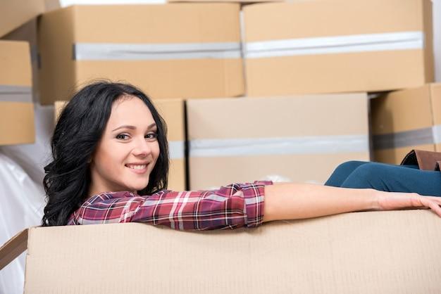 段ボール箱の新しいアパートの若い女性。