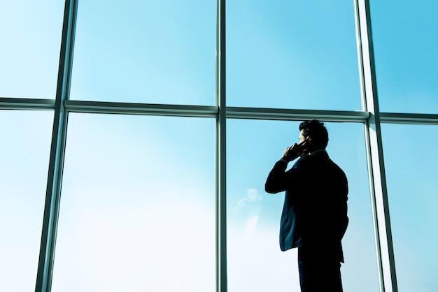 ビジネスマンは、パノラマの窓の外を見ています。