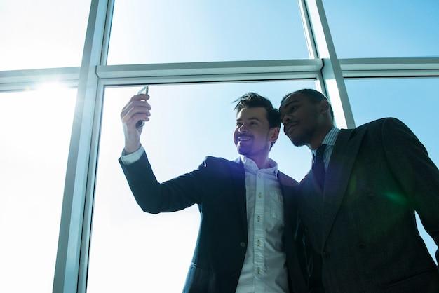 Бизнесмены делают селфи фото в современном офисе.