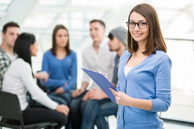 タブレットと人々のグループを持つ女性