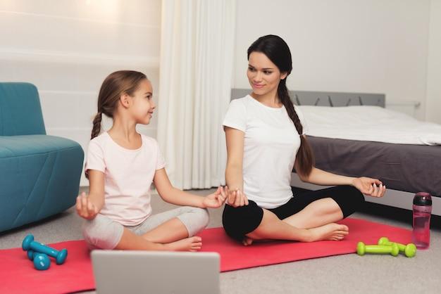 Практикуйтесь с молодой девушкой и матерью-йогой дома.